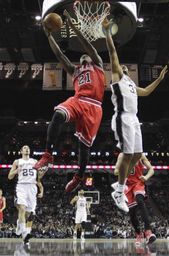 Chicago Bulls' Jimmy Butler (21) scores past San Antonio Spurs defender Boris Diaw  (33) during the first half of an NBA basketball game, Wednesday, Jan. 29, 2014, in San Antonio
