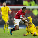 Manchester United's Antonio Valencia, centre, fights for the ball against Liverpool's Alberto Moreno during the English Premier League soccer match between Manchester United and Liverpool at Old Trafford Stadium, Manchester, England, Sunday Dec. 14, 2014