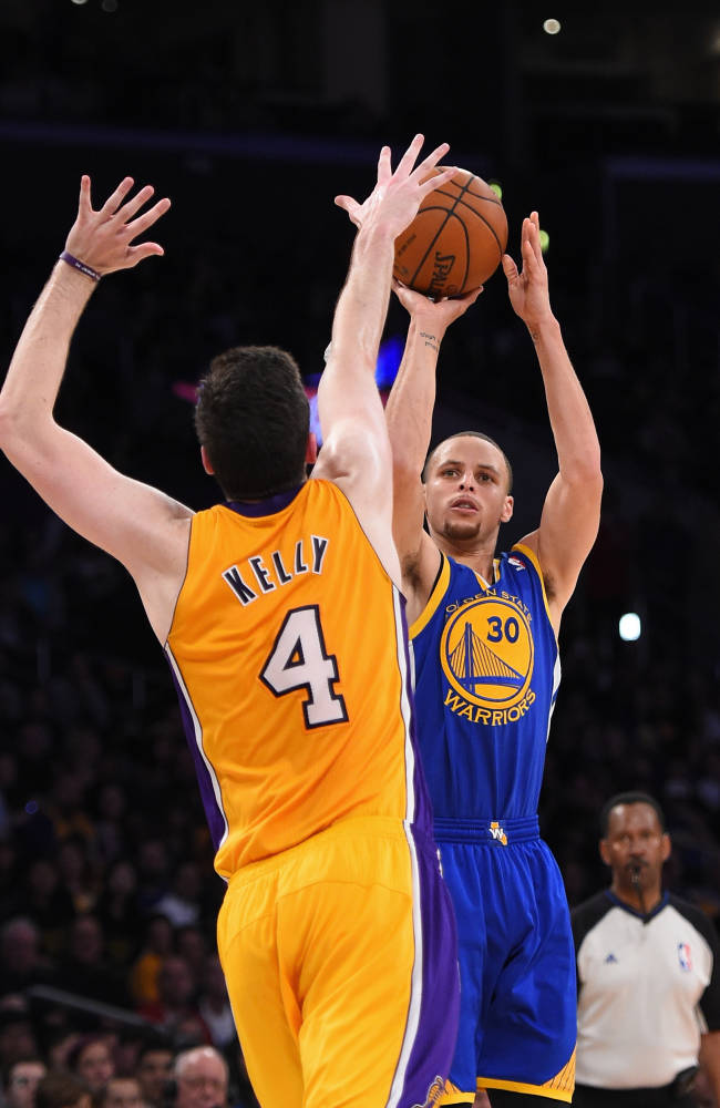 Golden State Warriors guard Stephen Curry shoots as Los Angeles Lakers forward Ryan Kelly defends during the second half of an NBA basketball game, Friday, April 11, 2014, in Los Angeles. The Warriors won 112-95