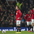 Manchester United players including Marouane Fellaini, right, Wayne Rooney, centre and Michael Carrick wait for play to restart after an early goal by Manchester City's Edin Dzeko, out of frame, during their English Premier League soccer match at Old Traf
