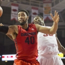 Dayton forward Devon Scott, left, corrals a rebound as Arkansas forward Moses Kingsley looks on during the first half of an NCAA college basketball game on Saturday, Dec. 13, 2014, in Fayetteville, Ark. (AP Photo/Gareth Patterson)