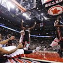 Toronto Raptors' DeMar DeRozan hits the floor after shooting against Miami Heat's Chris Bosh, center, and Dwyane Wade, right, during the second half of an NBA basketball game in Toronto, Friday, Nov. 29, 2013 The Associated Press