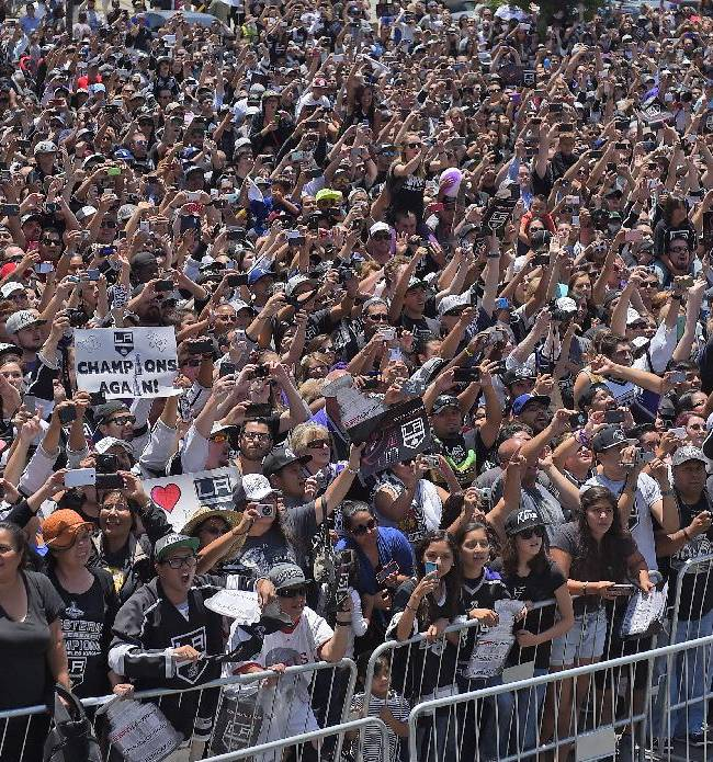 Fans of the Los Angeles Kings, cheer as the team rides by with the Stanley Cup trophy during a parade, Monday, June 16, 2014, in Los Angeles.  The parade and rally were held to celebrate the Los Angeles Kings' second Stanley Cup championship in three seasons