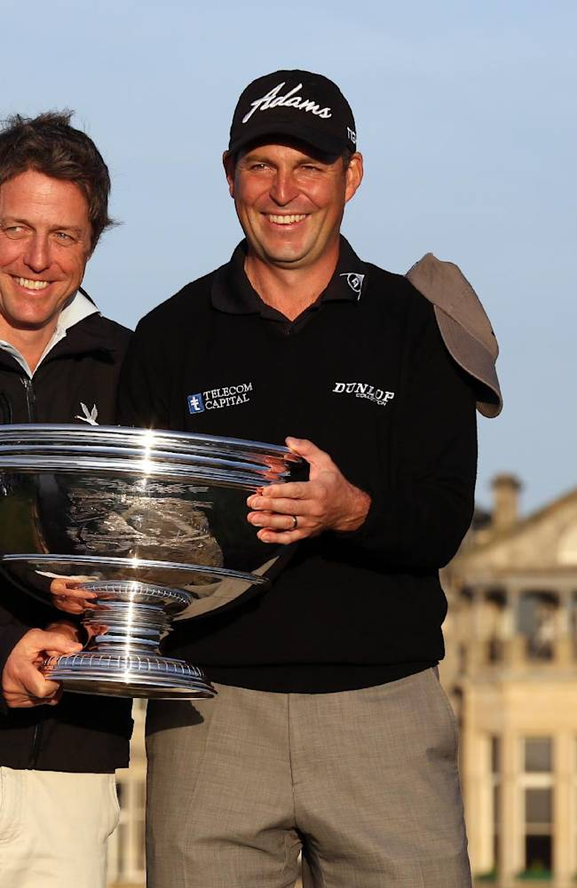 David Howell, right, with partner actor Hugh Grant after Howell was presented with the trophy after winning the 2013 Alfred Dunhill Links Championship at St Andrews Golf Course, St Andrews, Scotland, Sunday Sept. 29, 2013.  Howell was partnered by actor Hugh Grant for the Pro-Am Dunhill Team Event played alongside the individual Links Championship which Howell won.  England's David Howell ended a seven-year winless drought with a playoff victory over American Peter Uihlein to capture the Alfred Dunhill Links Championship on Sunday. (AP Photo / David Cheskin, PA)