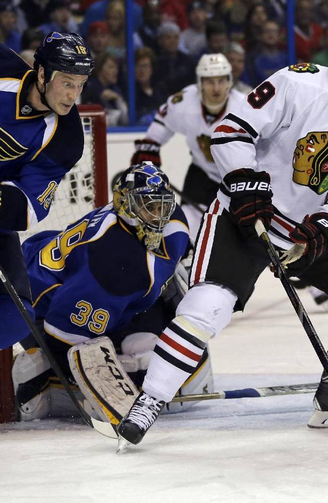Chicago Blackhawks' Jonathan Toews, right, controls the puck as St. Louis Blues goalie Ryan Miller and Jay Bouwmeester, left, defend during the third period in Game 1 of a first-round NHL hockey Stanley Cup playoff series Thursday, April 17, 2014, in St. Louis