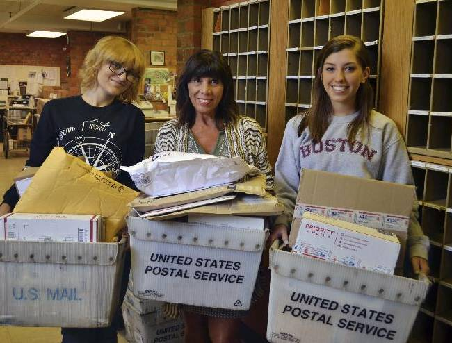 In this Aug. 4, 2014, photo provided by Saint Vincent College, student assistant Katie Nemchik, left, assistant manager Maria Schifano, center, and student assistant Ally Frye hold the bins of incoming mail for the NFL's Pittsburgh Steelers football players for that day at their training camp at Saint Vincent College, in Latrobe, Pa. The post office at the small college has been swamped with mail since wide receiver Antonio Brown vowed on Facebook to autograph anything fans send him