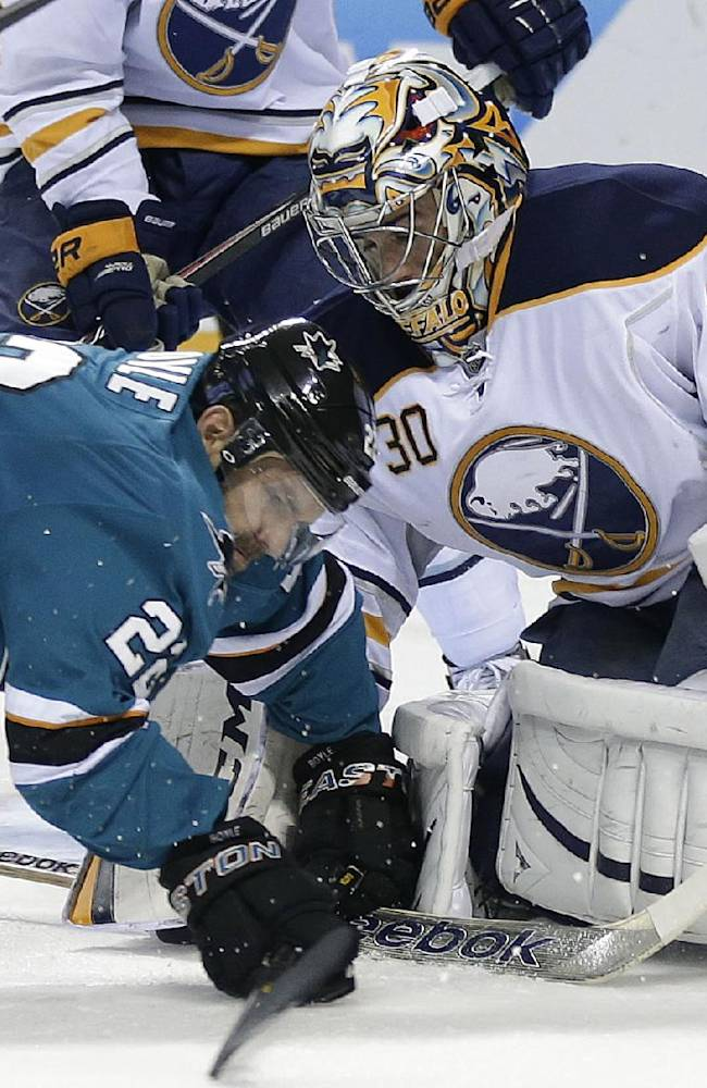 San Jose Sharks defenseman Dan Boyle, left, falls down in front of Buffalo Sabres goalie Ryan Miller (30) during the first period of an NHL hockey game Tuesday, Nov. 5, 2013, in San Jose, Calif