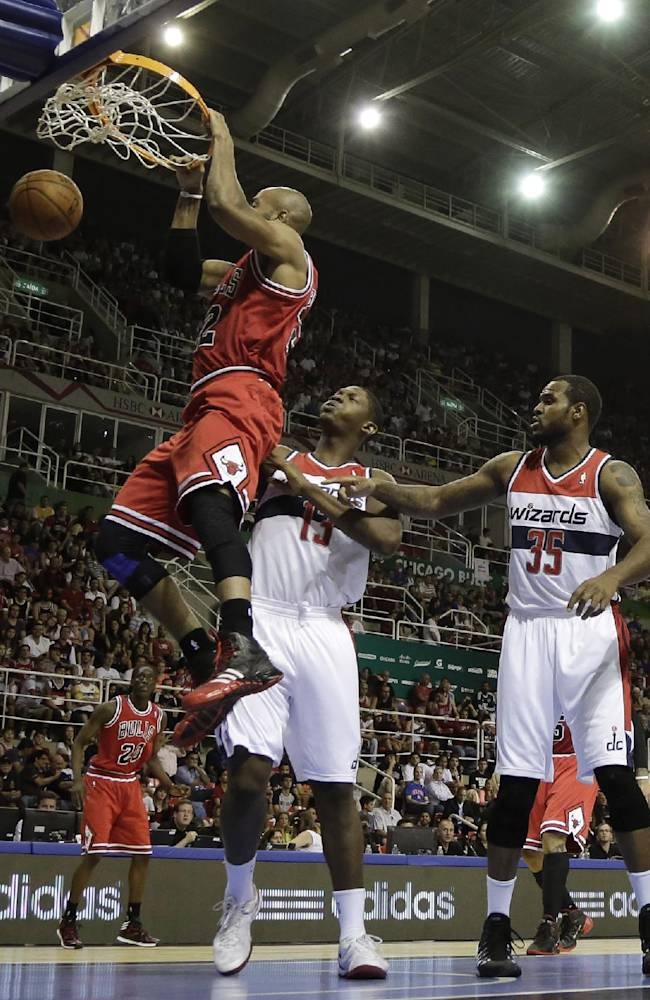 Chicago Bulls' Taj Gibson dunks the ball past Washington Wizards' Kevin Seraphin, center, and Trevor Booker, second from right, during the first half of an NBA preseason basketball game in Rio de Janeiro, Brazil, Saturday, Oct. 12, 2013