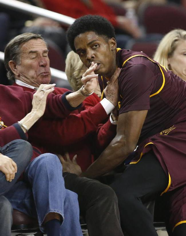 In this Jan. 9, 2014 file photo, Arizona State's Shaquielle McKissic runs into spectators sitting in courtside seats as he tries to prevent a ball from going out of bounds against Southern California during the second half of an NCAA college basketball game in Los Angeles. Oklahoma State All-American guard Marcus Smart is serving a three-game suspension for shoving a fan who later apologized for his actions. The incident shows how volatile the interaction between fans and athletes is becoming