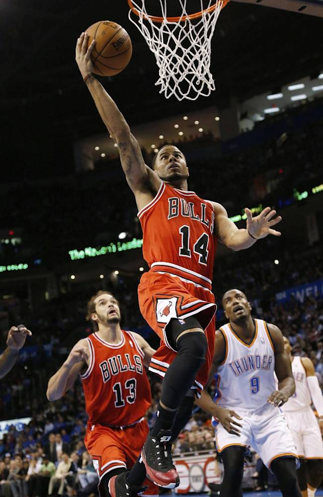 Chicago Bulls guard D.J. Augustin (14) shoots in front of Oklahoma City Thunder forward Serge Ibaka (9) and Bulls center Joakim Noah (13) during the first quarter of an NBA basketball game in Oklahoma City, Thursday, Dec. 19, 2013