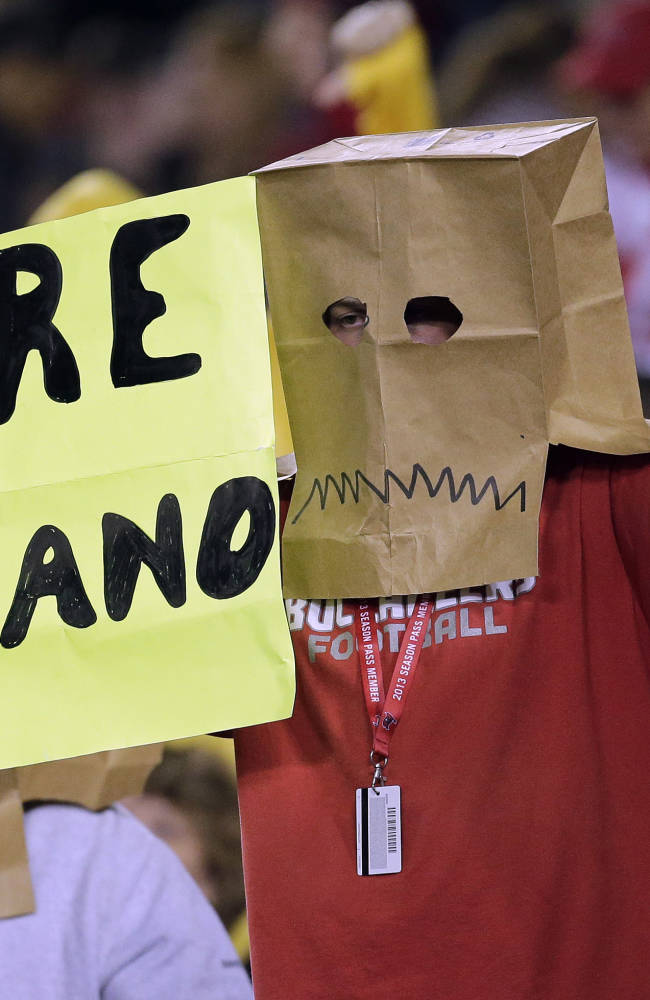 In this Oct. 24, 2013, file photo, a Tampa Bay Buccaneers fan wears a bag over his head and holds a sign calling for the firing of Tampa Bay coach Greg Schiano, during the fourth quarter of an NFL football game against the Carolina Panthers in Tampa, Fla