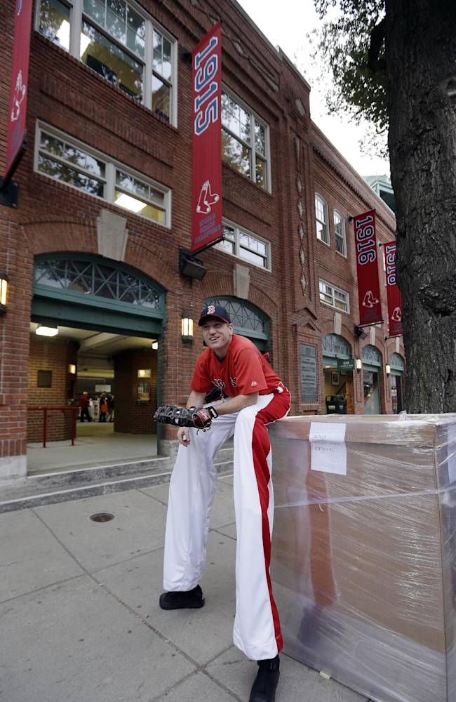 Brian Dwyer takes a break from walking on stilts outside Fenway Park  before Game 1 of baseball's World Series between the Boston Red Sox and the St. Louis Cardinals Wednesday, Oct. 23, 2013, in Boston