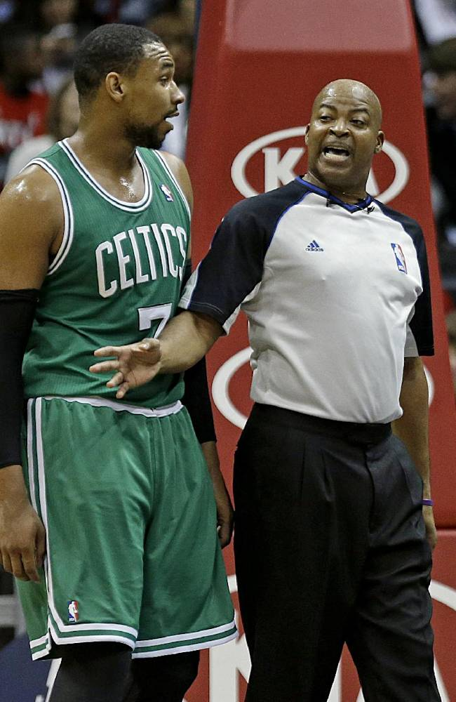Referee Michael Smith, right, holds back Boston Celtics' Jared Sullinger, after an altercation with Atlanta Hawks' DeMarre Carroll, not pictured, during the third quarter of an NBA basketball game, Saturday, Nov. 23, 2013, in Atlanta. Sullinger was called for a flagrant foul on the play