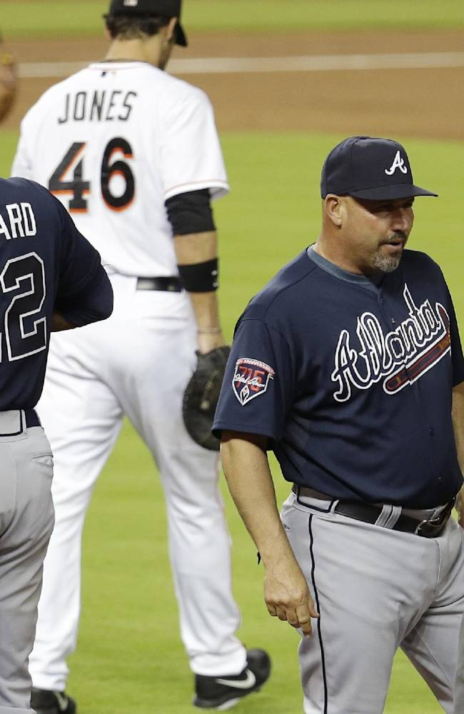Atlanta Braves manager Fredi Gonzalez, front center, talks with first base umpire Jim Reynolds, right, after Jason Heyward (22) was ruled safe at first with a single in the third inning of a baseball game against the Miami Marlins, Thursday, May 1, 2014, in Miami