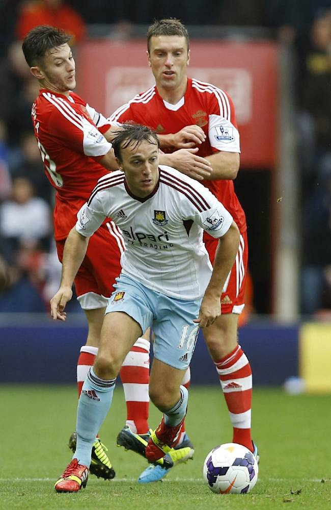West Ham's Mark Noble moves the ball away from Southampton's Rickie Lambert, right, and Adam Lallana, left, during the English Premier League soccer match between Southampton and West Ham United at St Mary's Stadium in Southampton, England Sunday, Sept. 15, 2013