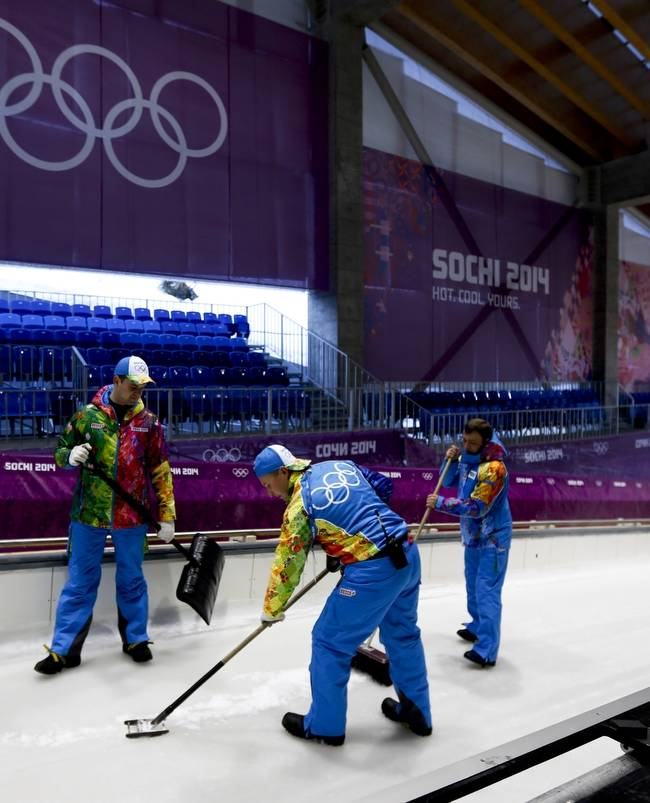 Workers prepare the ice at the Sanki Sliding Center, which will host the bobsleigh, skeleton and luge competitions at the 2014 Winter Olympics, Monday, Feb. 3, 2014, in Krasnaya Polyana, Russia