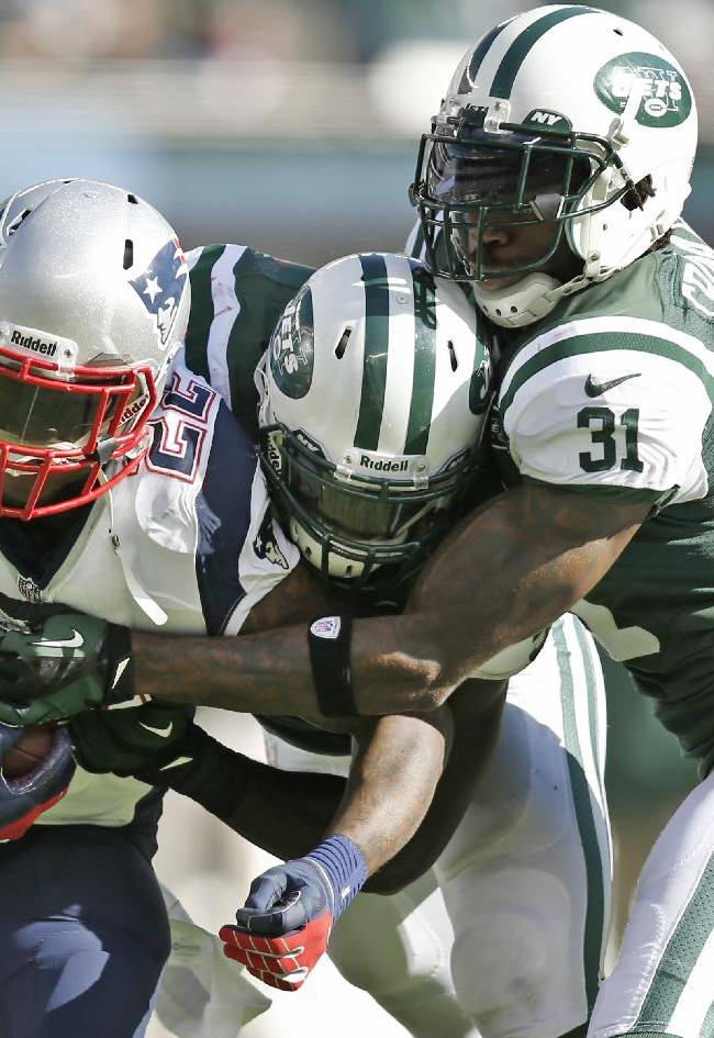 In this Oct. 20, 2013, file photo, New England Patriots' Stevan Ridley (22) is tackled by New York Jets' DeMario Davis, center, and Antonio Cromartie (31) during the second half of an NFL football game in East Rutherford, N.J. Davis, only in his third NFL season, is considered one of the Jets' main leaders despite still being a youngster in the locker room