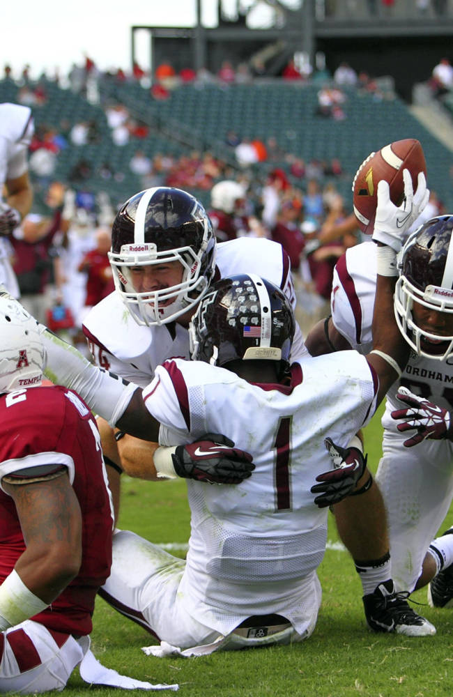 In this photo taken on Sept. 14, 2013, and provided by Fordham University, Fordham's Brian Wetzel (24) and Carlton Koonce (21) celebrate with Sam Ajala (1) after Ajala hauled in a 29-yard touchdown pass with four seconds left in the fourth quarter to tie the score at 29-29 against Temple in a college football game in Philadelphia. The Rams added the extra point to win 30-29, and are 7-0 for the first time since 1930