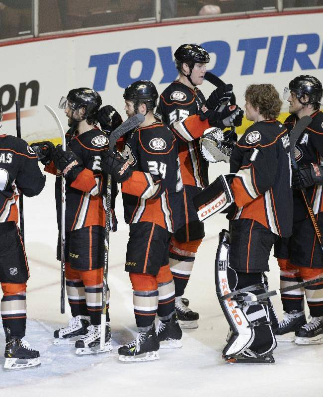 Anaheim Ducks players celebrate their team's 5-2 win against the San Jose Sharks after an NHL hockey game on Wednesday, April 9, 2014, in Anaheim, Calif. The Ducks clinched their second straight Pacific Division title
