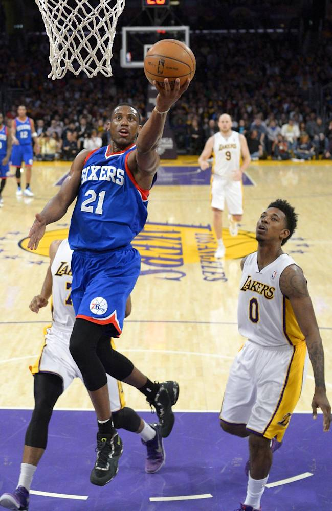 Philadelphia 76ers forward Thaddeus Young, left, puts up a shot as Los Angeles Lakers forward Nick Young defends during the first half of an NBA basketball game, Sunday, Dec. 29, 2013, in Los Angeles