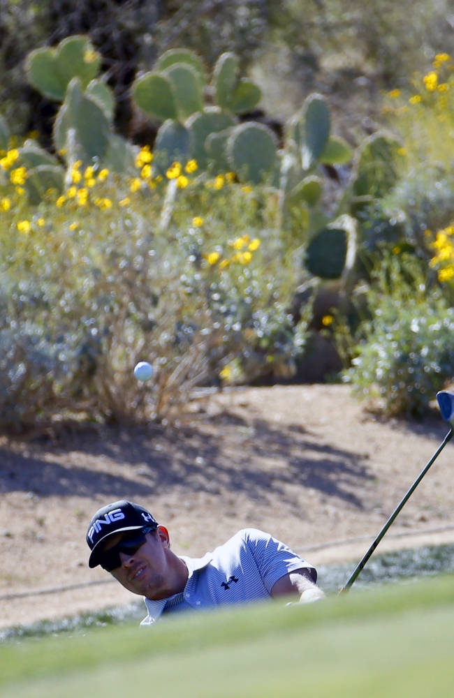 Hunter Mahan, hits a chip shot on the 15th hole in his match against Richard Sterne, of South Africa, during the second round of the Match Play Championship golf tournament on Thursday, Feb. 20, 2014, in Marana, Ariz