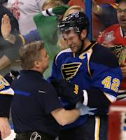St. Louis Blues center David Backes (42) is tended to by trainer Ray Barile after taking a hit from Chicago Blackhawks defenseman Brent Seabrook in the third period during Game 2 of a first-round NHL hockey playoff series on Saturday, April 19, 2014, in St. Louis. Seabrook was assessed a game misconduct penalty for the play and the Blues scored the tying goal on the ensuing five-minute power play. Backes left the ice under his own power. (AP Photo/St. Louis Post-Dispatch, Chris Lee)
