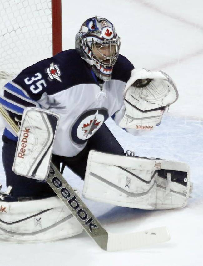 Winnipeg Jets goalie Al Montoya makes a glove save during the first period of an NHL hockey game against the Chicago Blackhawks, Sunday, Jan. 26, 2014, in Chicago