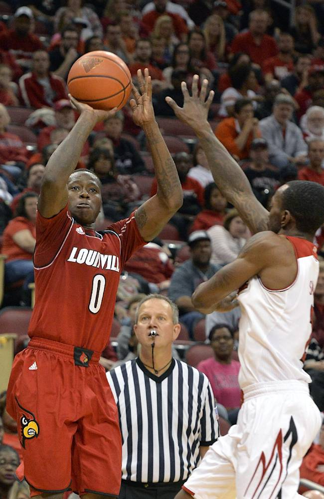 Louisville'sTerry Rozier, left, gets a shot off over the defense of Russ Smith during their NCAA college basketball scrimmage Saturday, Oct. 19, 2013, in Louisville, Ky