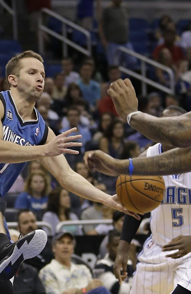 Minnesota Timberwolves' J.J. Barea, left, passes the ball between Orlando Magic's Victor Oladipo (5) and Kyle O'Quinn, right, during the first half of an NBA basketball game in Orlando, Fla., Saturday, April 5, 2014