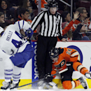 Toronto Maple Leafs' Morgan Rielly, left, and Philadelphia Flyers' Matt Reid, right, try to get at the puck trapped between the skates of linesman Tim Nowak, center, in the third period of an NHL hockey game, Saturday, Jan. 31, 2015, in Philadelphia. The