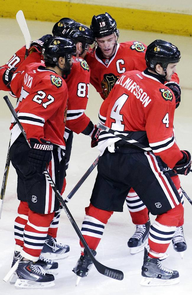 Chicago Blackhawks' Jonathan Toews (19) celebrates with teammates after scoring a goal against the Minnesota Wild during the third period in Game 5 of an NHL hockey second-round playoff series in Chicago, Sunday, May 11, 2014. The Blackhawks won 2-1