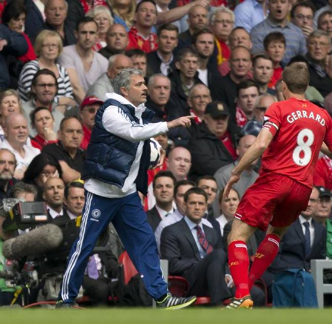 Chelsea's manager Jose Mourinho, left, keeps the ball from Liverpool's Steven Gerrard during their English Premier League soccer match at Anfield Stadium, Liverpool, England, Sunday April 27, 2014