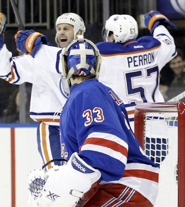 Edmonton Oilers' Ryan Smyth (94) celebrates with teammate David Perron (57) as New York Rangers goalie Cam Talbot (33) watches after Smyth scored during the first period of an NHL hockey game on Thursday, Feb. 6, 2014, in New York