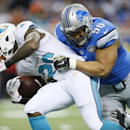 Detroit Lions defensive tackle Ndamukong Suh (90) stops Miami Dolphins running back Lamar Miller (26) during the first half of an NFL football game in Detroit, Sunday, Nov. 9, 2014 The Associated Press