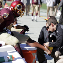 Washington Redskins running back Alfred Morris, left, has his foot taped during the first half of an NFL football game against the Tennessee Titans, Sunday, Oct. 19, 2014, in Landover, Md The Associated Press
