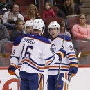 Edmonton Oilers' Ryan Nugent-Hopkins, right, celebrates his goal against the Arizona Coyotes with teammates Teddy Purcell (16) and Justin Schultz, left, during the first period of an NHL hockey game Tuesday, Dec. 16, 2014, in Glendale, Ariz The Associated