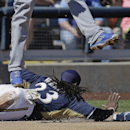 Milwaukee Brewers' Rickie Weeks slides safely back to third as Kansas City Royals third baseman Mike Moustakas leaps for a high throw during the first inning of an exhibition spring training baseball game Saturday, March 8, 2014, in Phoenix The Associated