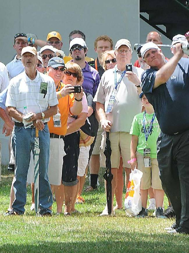 Jim Justice hits his second shot on the first hole during The Greenbrier Classic golf tournament in White Sulphur Springs, W.V., Wednesday, July 2, 2014