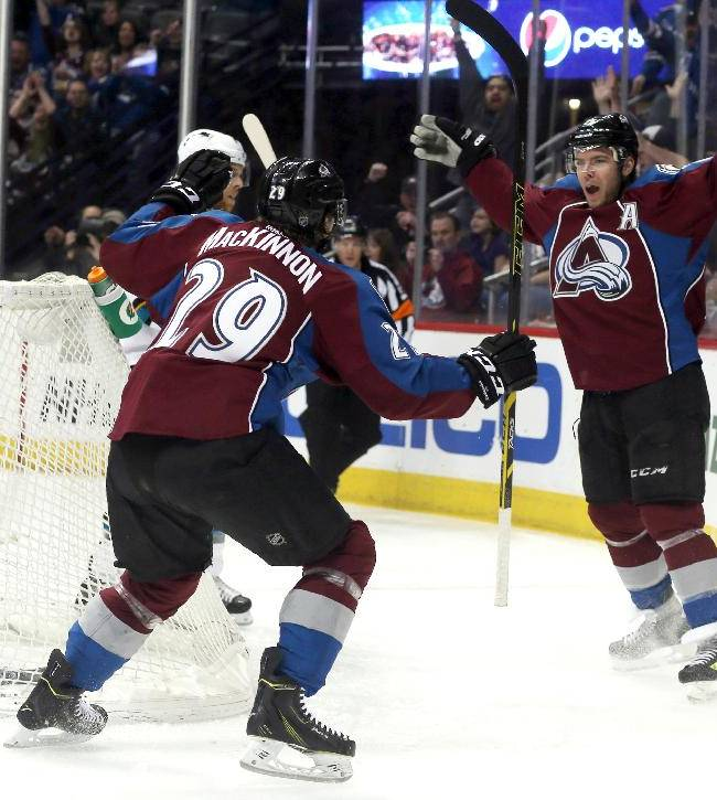 Colorado Avalanche center Nathan MacKinnon, left, celebrates with teammate Paul Stastny after his goal against the San Jose Sharks in the first period of an NHL hockey game on Saturday, March 29, 2014, in Denver