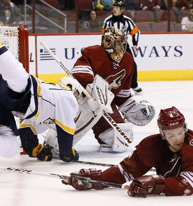 Phoenix Coyotes' Zbynek Michalek, right, of Czech Republic, sends Nashville Predators' Patric Hornqvist, left, of Sweden, up in the air in front of Coyotes goalie Thomas Greiss, of Germany, during the first period of an NHL hockey game on Thursday, Oct. 31, 2013, in Glendale, Ariz