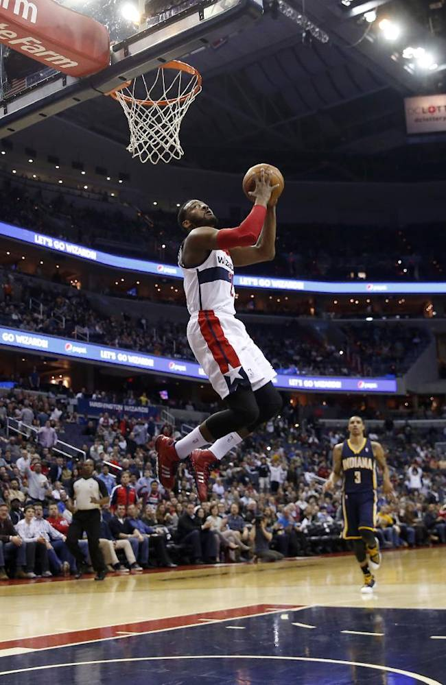 Washington Wizards guard John Wall dunks in the first half of an NBA basketball game against the Indiana Pacers, Friday, March 28, 2014, in Washington