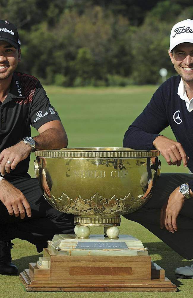 Jason Day, left, of Australia and compatriot Adam Scott pose with the World Cup of Golf trophy for photographers after winning the team event at Royal Melbourne Golf Course in Australia, Sunday, Nov. 24, 2013