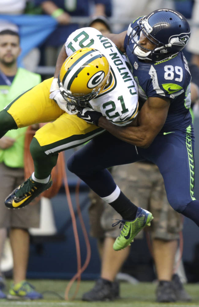 Seattle Seahawks' Doug Baldwin, right, breaks up an interception attempt by Green Bay Packers free safety Ha Ha Clinton-Dix (21) in the first half of an NFL football game, Thursday, Sept. 4, 2014, in Seattle