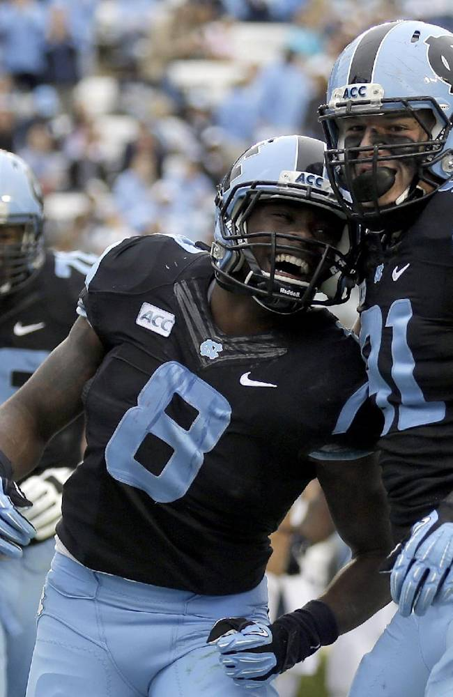 North Carolina's Allen Champagne, right, and T.J. Logan (8) celebrate Logan's touchdown against Old Dominion during the first half of an NCAA college football game in Chapel Hill, N.C., Saturday, Nov. 23, 2013. North Carolina won 80-20