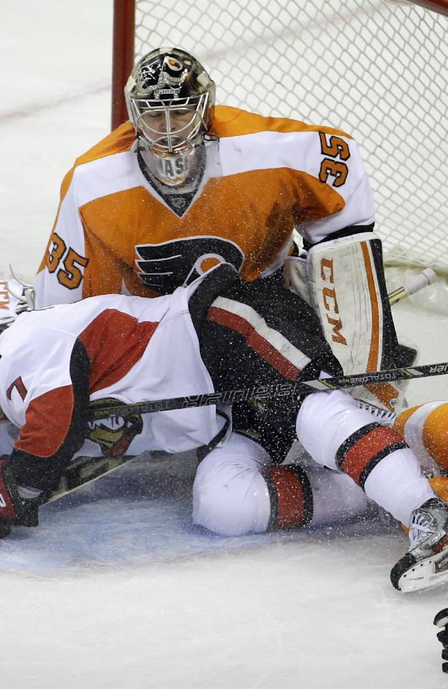Ottawa Senators' Kyle Turris (7) and Philadelphia Flyers' Kimmo Timonen (44), of Finland, slide into Steve Mason (35) during the third period of an NHL hockey game, Tuesday, Nov. 19, 2013, in Philadelphia. Philadelphia won 5-2