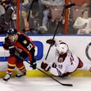 Florida Panthers center Scott Gomez (23) and Phoenix Coyotes right wing David Moss (18) battle for the puck during the second period of an NHL hockey game, Tuesday, March 11, 2014, in Sunrise, Fla. (AP Photo/Wilfredo Lee)