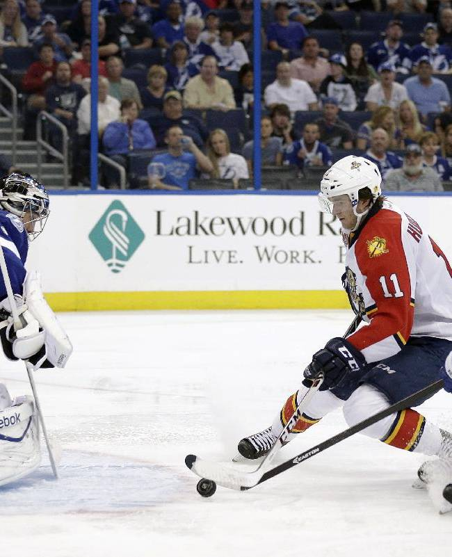 Florida Panthers center Jonathan Huberdeau (11) prepares to shoot the puck past Tampa Bay Lightning goalie Ben Bishop (30) for a goal after getting past right wing Richard Panik (71), of Slovakia, during the third period of an NHL hockey game Thursday, Oct. 10, 2013, in Tampa, Fla. The Lightning won 7-2