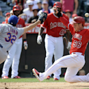 Los Angeles Angels' Kole Calhoun, right, slides safely into home as New York Mets pitcher John Lannan, left, lunges to catch the ball during the eighth inning of a baseball game in Anaheim, Calif., Sunday, April 13, 2014. The play was the result of a wild