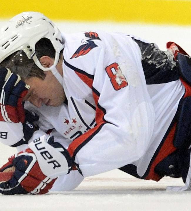 Washington Capitals' Alex Ovechkin holds his head as he lies on the ice after taking a hit while playing the Winnipeg Jets during preseason NHL hockey game in Belleville, Ontario, on Saturday, Sept. 14, 2013
