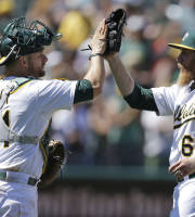 Oakland's Stephen Vogt, left, and pitcher Sean Doolittle enjoy the moment after beating Texas on Wednesday. (AP Photo)